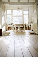 View through double doors of kitchen-cum-living room with antique chairs and white-painted dining table
