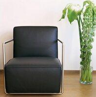 Schwarzer Ledersessel mit Stahlrohr-Rahmen neben Bodenvase mit grünen Blättern