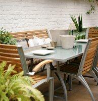 Moderne Gartenmöbel-Garnitur aus Metall und Holz auf einer Terrasse