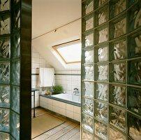 Blick durch Wand aus Glasbausteinen in Bad ensuite mit Dachflächenfenster über der eingebauten Wanne