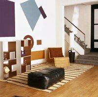 Kleine Sitzecke in offenem Wohnraum mit Leder-Sitzpolster und Regalsystem vor grafischen Mustern an der Wand
