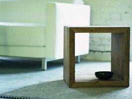 Würfelförmiges Holzregal mit kleiner Schale auf dem Boden vor einem weißem Sofa