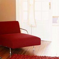 Rote Chaise longue mit zierlichem Stahlgestell und Stehlampe vor weisser Altbautür