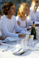 Friends sitting at table laid for special occasion with champagne