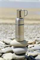 Thermos flask on pebbles