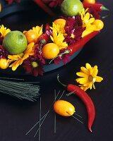 Arrangement of flowers and citrus fruit