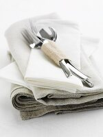 Cutlery on a pile of linen cloths