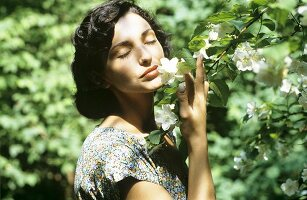 Woman smelling branch of fragrant blossom