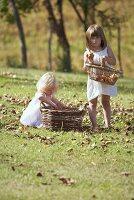 Zwei kleine Mädchen sammeln Äpfel auf der Wiese