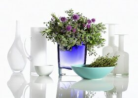 Various glass vases, one with bunch of herbs