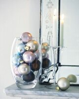 Christmas baubles in glass vase beside candle on mantelshelf