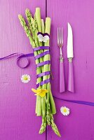 Green asparagus tied with a bow on a purple wooden surface