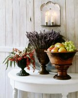 Decorative vases of fruit, lavender and berries on table