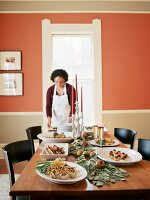 Cook putting plate on buffet table in living room