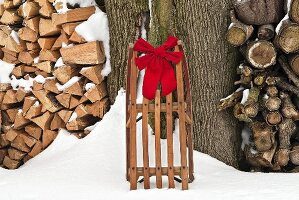Antique Sled with Red Bow Leaning Against a Tree in the Snow