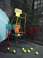 A random stack of metal chairs in various colours in front of a grey stone wall