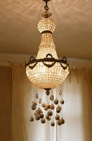 A crystal chandelier decorated with Christmas baubles