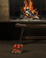 A pair of red shoes in front of a roaring fire