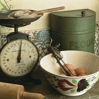 An old pair of kitchen scales with eggs and an old hand mixer