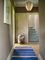 Bright gray foyer in a country home with blue carpet runners and bright blue wooden stairs