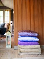 Stack of pillows with shiny silk fabric in front of a brown wood paneled wall next to a passage with a view into the living room
