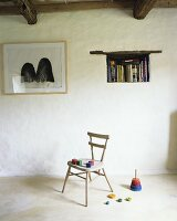 Colorful wooden blocks on an old wooden chair, a throwing game, books in a wall niche and a picture on the wall