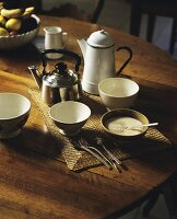 Ceramic bowls, a kettle and an enamel jug on a wooden table
