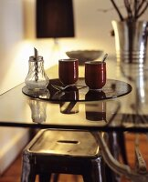 Two mugs and a sugar shaker on a glass table