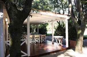 Trees in front of white wooden terrace with posts and a patio table on a raised wooden platform