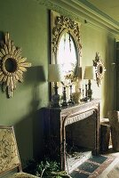 An elaborate mirror hung on a green wall above a mantelpiece