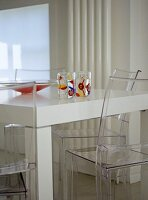 Modern dining room with white walls and table and perspex chairs.