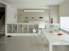 Modern, white open plan kitchen diner with glass fronted cupboard units and table with perspex chairs.