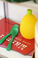 A lemon juice bottle and green plastic spoon on a red chopping board