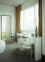 Hotel bedroom with retro styled dressing table and white plastic chair