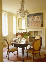 Dining room with white panelled walls and antique table and chairs under chandelier.