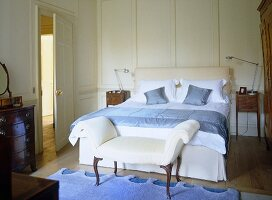 Blue and white bedroom with antique furniture an panelled walls.