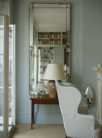 A detail of a traditional sitting room, upholstered wing back armchair, Venetian mirror, side table