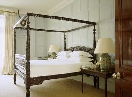 A traditional bedroom with painted panelling, carved wooden four poster bed, bedside table, lamps