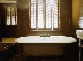 A detail of a traditional, bathroom, a free standing roll top bath, window shutters