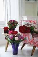 Various bunches of flowers in coloured glass vases next to a 1950s style armchair