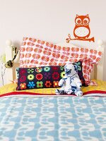 A child's bed with colourful cushions, a soft toy and a head phones