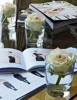 A rose in a glass of water next to a fashion magazine
