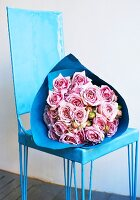 A bunch of roses in blue paper on a blue chair