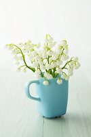 Lily of the valley in a turquoise cup
