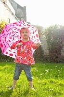Little girl with umbrella in garden