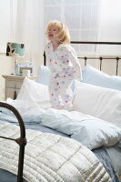 Little girl in pajamas standing on a bed
