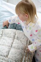 Little girl tucking her plush animals into bed