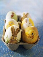 Easter eggs painted with animal motifs in an egg box
