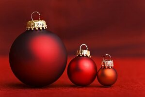 Three Christmas baubles in shades of red