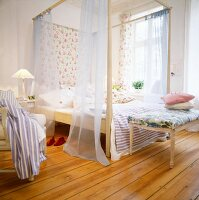 A bedroom with floor boards and a four poster bed with chiffon curtains